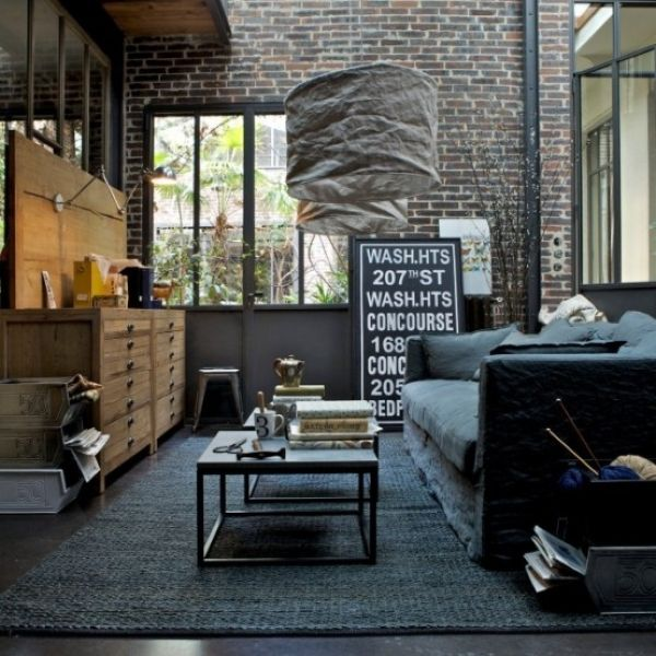 Industrial Living Room Design Idea with Brick Walls and A Dark Concrete Floor