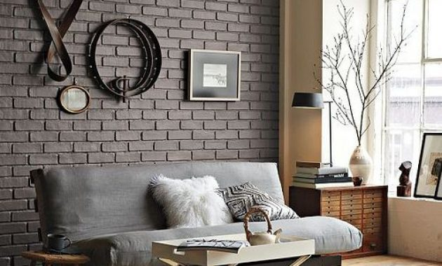 contemporary living room with a grey brick wall and leather and metal