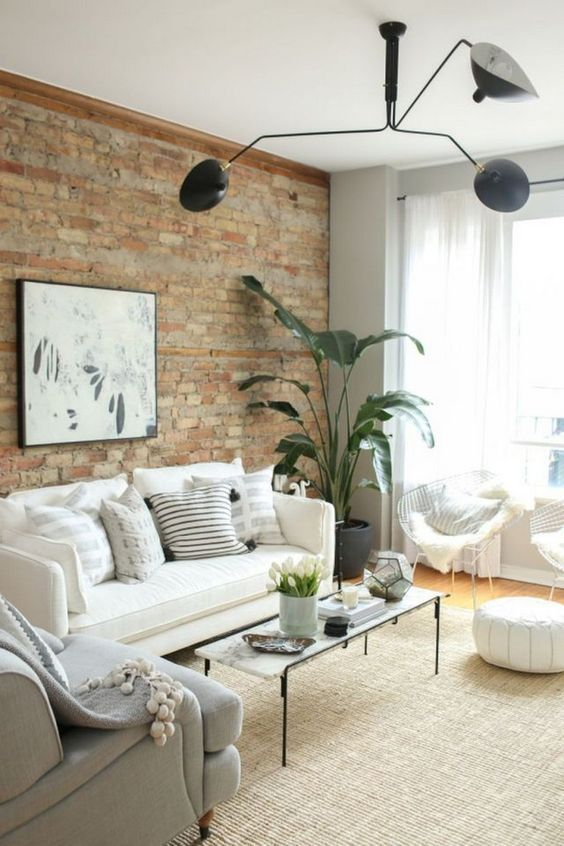 Living Room With Potted Greenery And Exposed Brick Wall