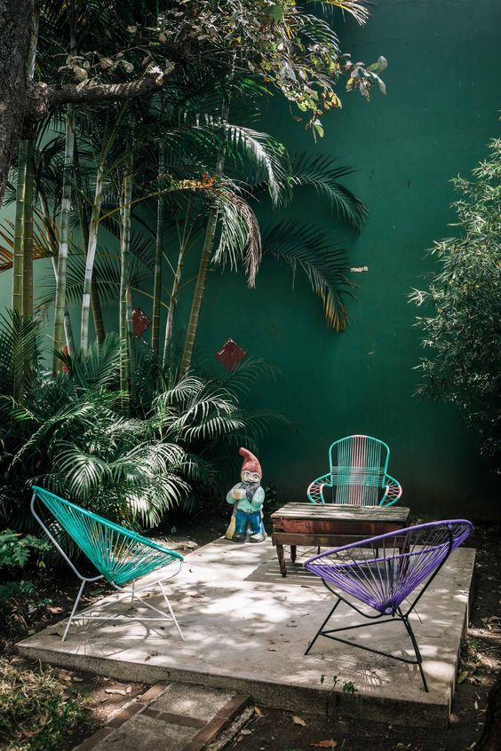 Tropical Patio With Colorful Chairs And Vintage Wooden Table