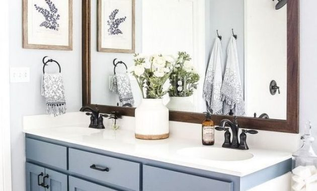 Cozy Farmhouse Bathroom With A Serenity Blue Vanity And A Tub