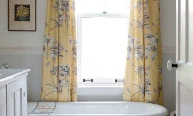 Small Farmhouse Bathroom With A White Vanity And A Yellow Clawfoot Bathtub