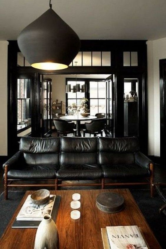Cozy Dark Masculine Room With A Black Leather Sofa And A Wooden Coffee Table
