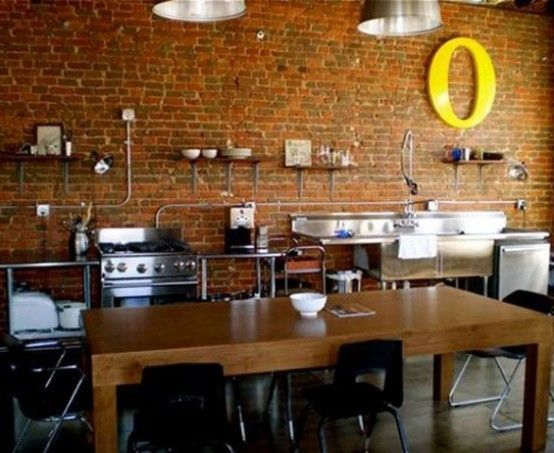 Fully Industrial Kitchen With A Red Brick Wall And Shiny Metal Surfaces