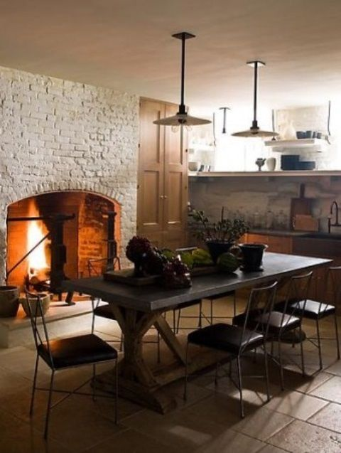 Kitchen With Large Fireplace Clad With White Brick And A Concrete Table