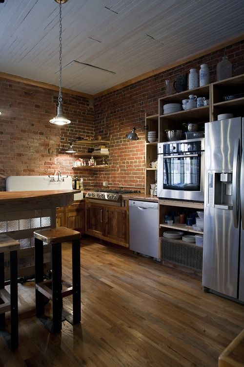 Kitchen With Red Brick Walls And Rich Stained Wood Floor