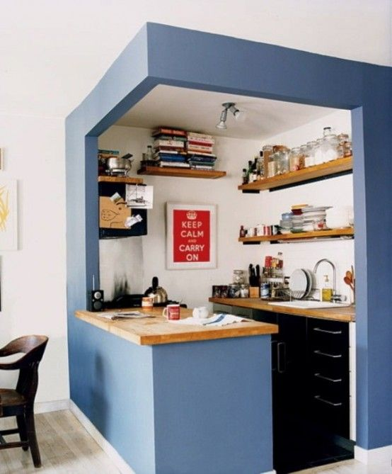 Small Kitchen Placed In A Blue Cube And With Built-In Black Cabinets