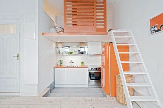 Small Kitchen With White Cabinets And A Bright Orange Fridge