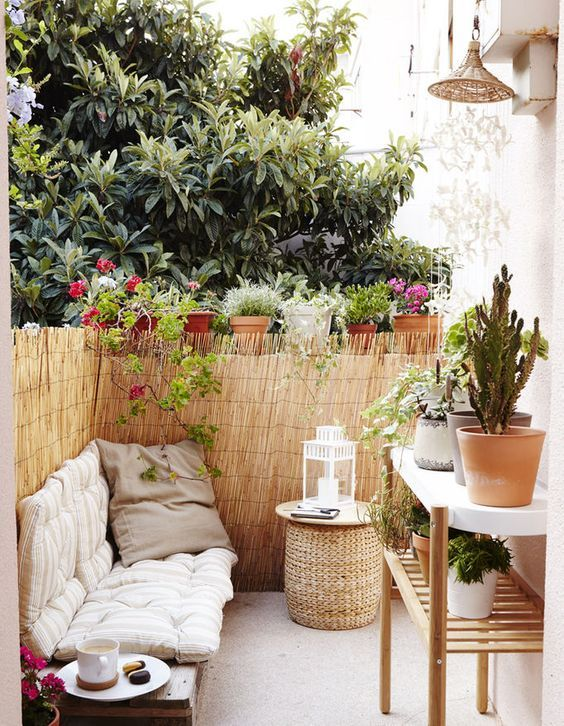 Small Terrace Design Ideas With A Wicker Ottoman And A Large Plant Stand