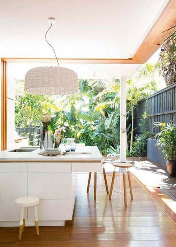Tropical Garden With Sleek White Kitchen Island And A White Wicker Lampshade