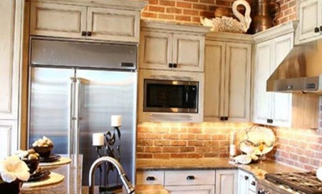 Vintage Kitchen With Red Brick Wall And Neutral Vintage Cabinets