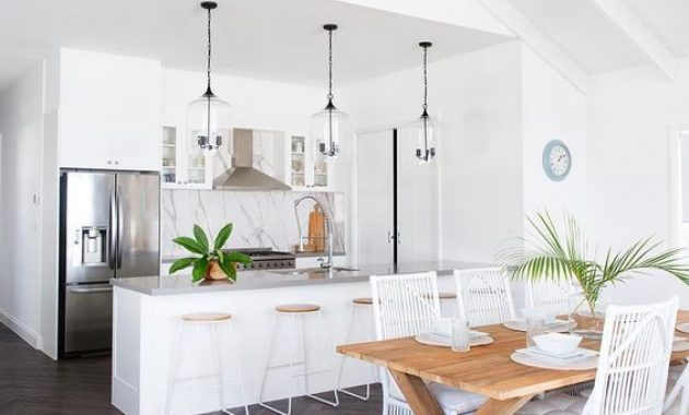 White Tropical Kitchen With A Marble Backsplash And Glass Pendant Lamps