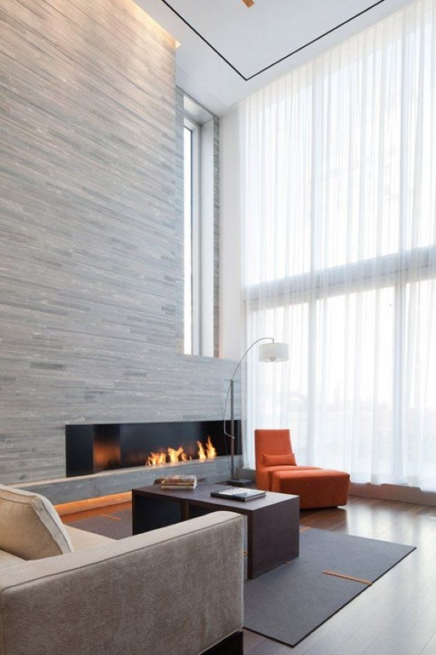 Double-Height Minimalist Living Room With A Wood Clad Fireplace Wall
