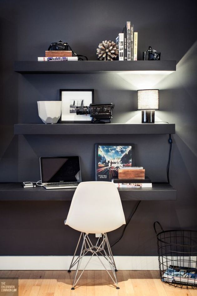 Home Office With Black Wall With Floating Shelves And A Desk With Displays