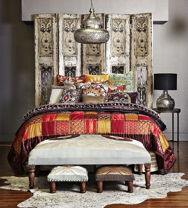 Moroccan Bedroom With Ornate Wooden Screen Plus Ottomans And Bright Printed Textiles