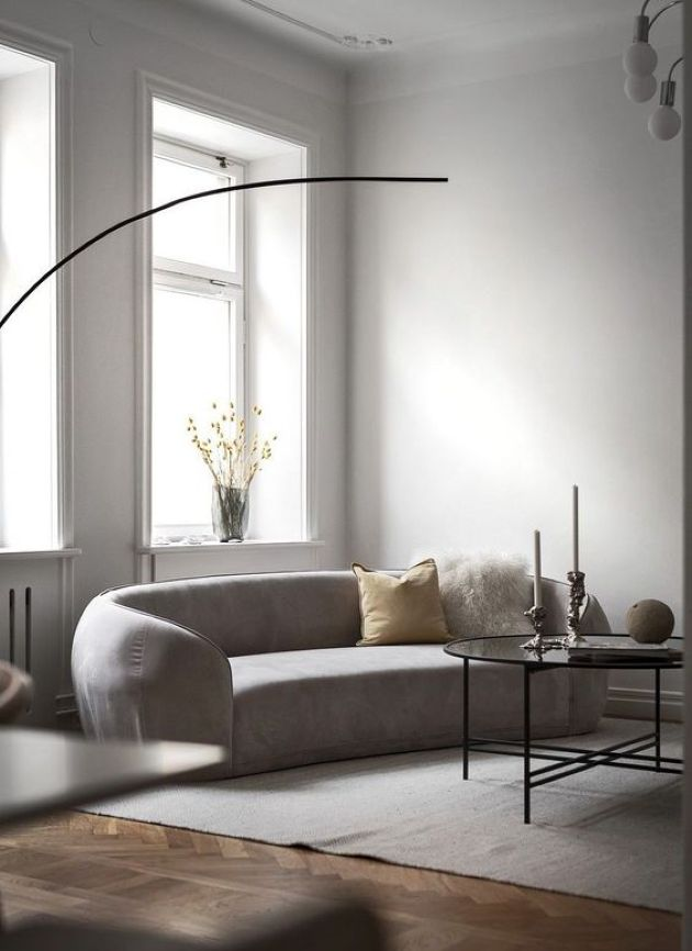 Neutral Minimalist Living Room With A Curved Sofa And A Pendant Lamp