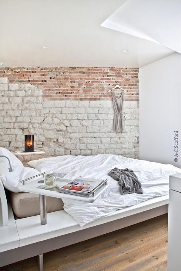 Ultra-Modern Bedroom With A Chic Bed And A Faux Stone And Brick Wall