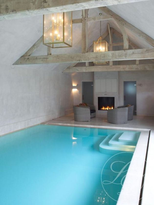 Blue Indoor Pool With A Poolside Fireplace