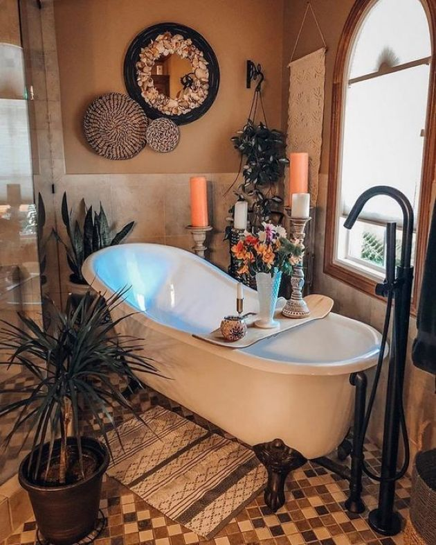 Boho Bathroom With A Clawfoot Tub And Candles Plus Potted Plants