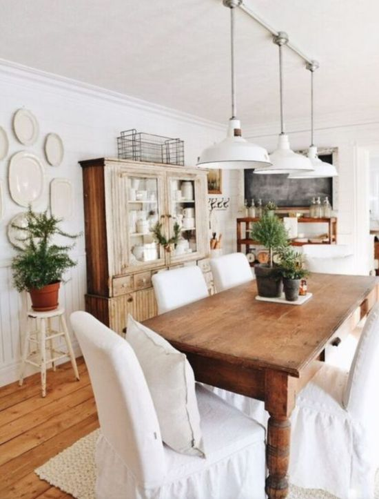 Farmhouse Dining Area With Stained Furniture And White Covered Chairs Plus Potted Greenery And White Pendant Lamps