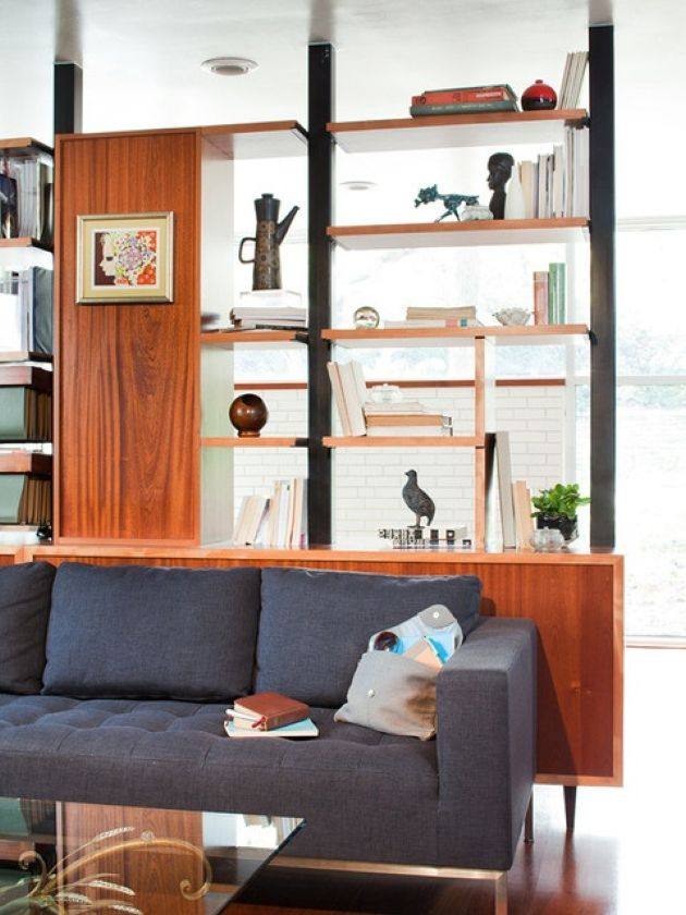 Large Storage Unit That Acts As A Space Divider Plus Open Shelves And Storage Compartments