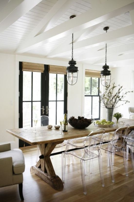 Modern Farmhouse Dining Room With A Wooden Table And Wicker Shades Plus Ghost Chairs And Vintage Lanterns And Black Doors