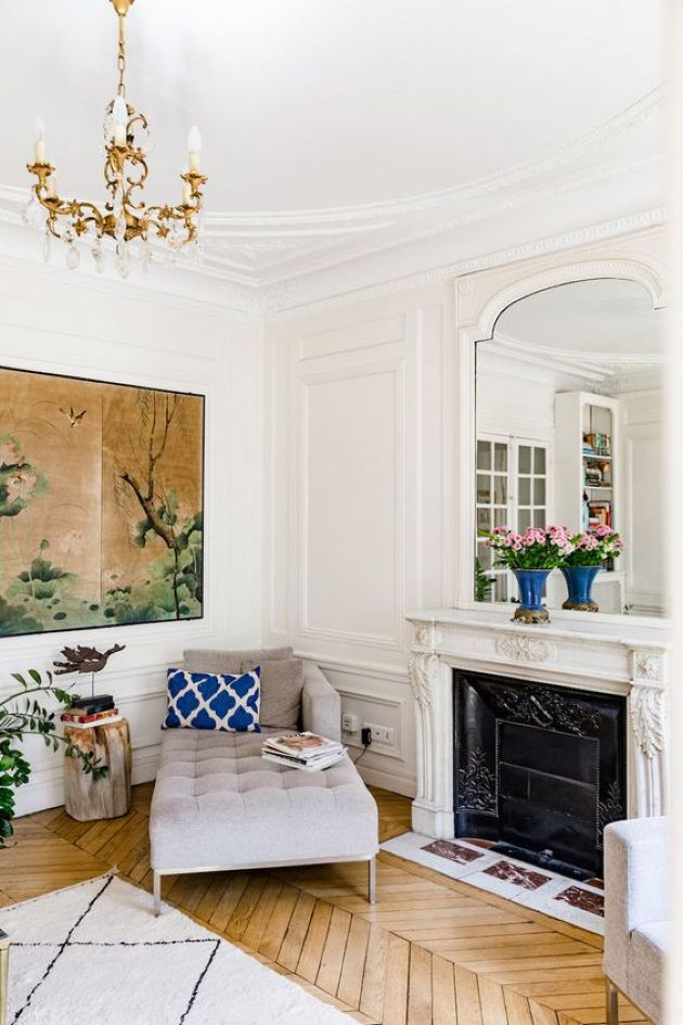 Parisian Chic Living Room Décor With White Walls With Molding And Warm-Colored Hardwood Parquet Floors