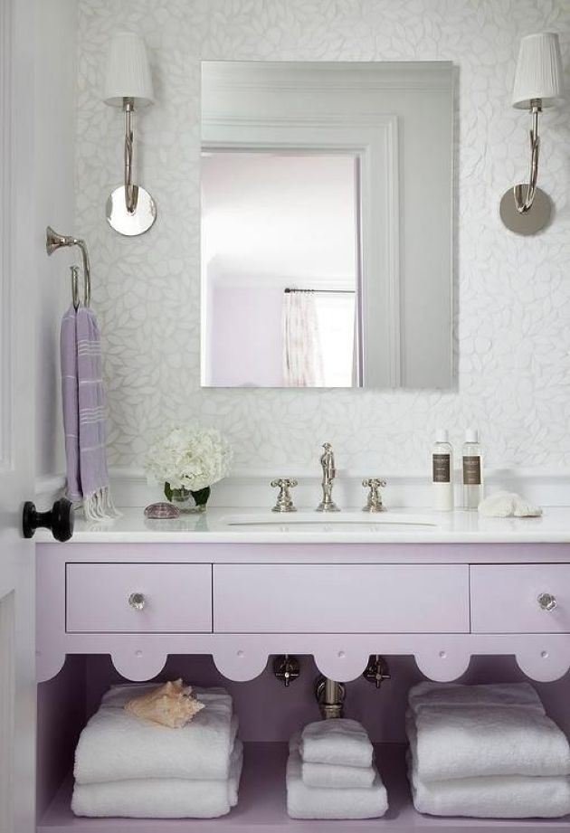Romantic Bathroom With A Lavender Vanity And White Stone Countertop