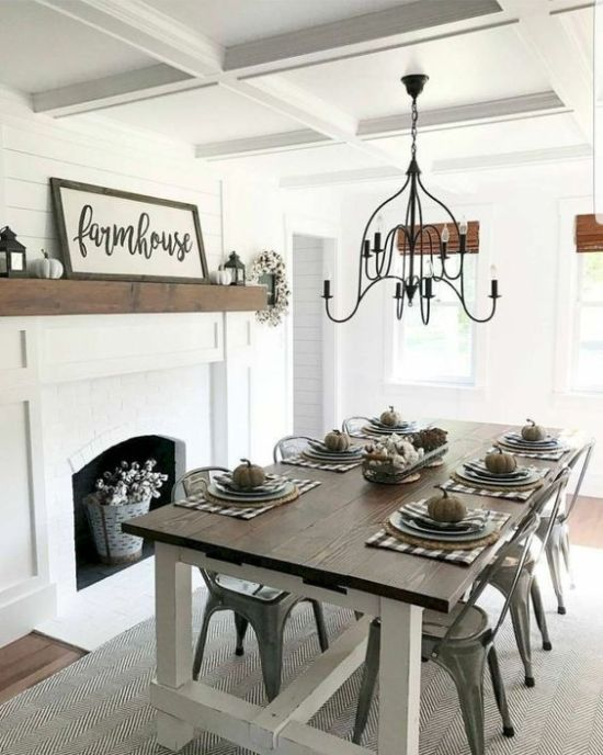 Simple Modern Farmhouse Dining Area With A White Fireplace And Signs And Pumpkins Plus A Wooden Table And Metal Chairs