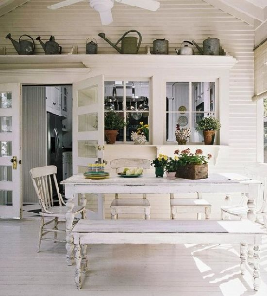 White Farmhouse Dining Space With Shabby Chic Furniture And Watering Cans For Décor Plus Potted Greenery And Blooms