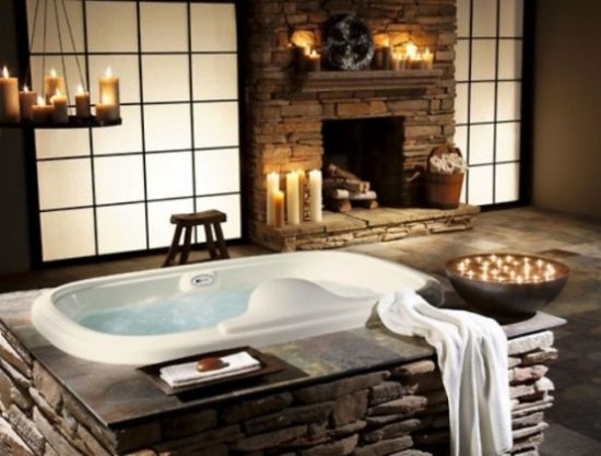 A Bathtub And A Fireplace Clad With Decorative Stone Plus Lots Of Candles That Create A Mood And An Atmosphere