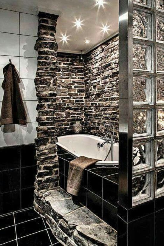 A Bold Bathroom Clad With Natural Dark Stone And With Black Tiles That Are Highlighted With White Grout
