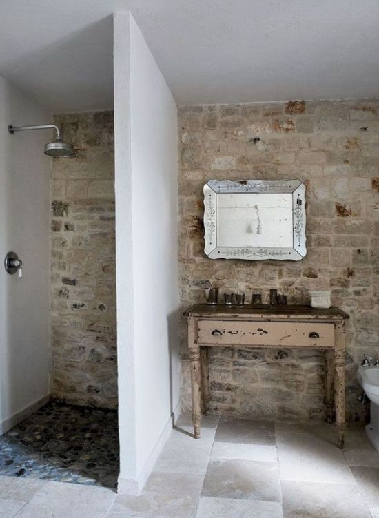 A Farmhouse Bathroom With A Stone Wall Tiled Floor A Shabby Chic Vanity And A Gorgeous Refined Mirror