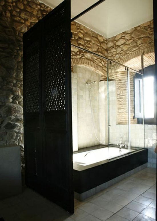 A Modern Bathroom With Stone Clad Walls A Modern Black Shower Space With A Black Space Divider
