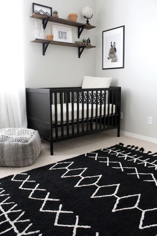 Chic Nursery With A Black Crib And Printed Rug