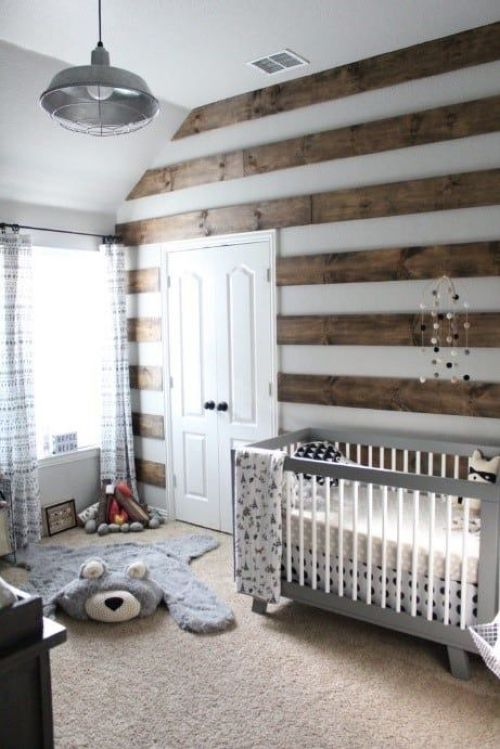 Chic Woodland Nursery With A Striped Stained Wood Wall Layered Rugs A Grey Vintage Crib A Pendant Lamp And Lace Curtains
