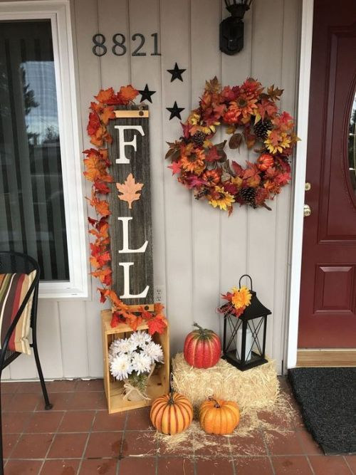 Creative And Unique Fall Sign To Welcome Autumn With A Reclaimed Wood Fall Sign Topped With Bright Fake Leaves Plus Faux Pumpkins And A Wreath Plus Hay And A Lantern