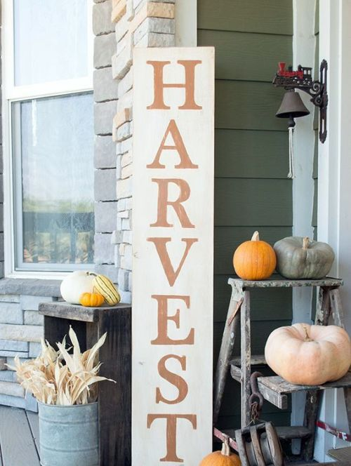Creative And Unique Fall Sign To Welcome Autumn With A Tall Harvest Sign Plus Corn Husks In A Bucket And Various Colorful Pumpkins Around
