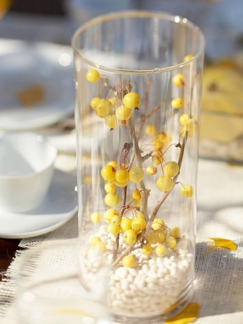Fall Home Décor Idea With A Clear Vase Filled With White Beads And With Branches With Yellow Berries Inside