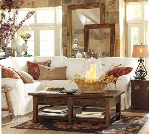 Fall Living Room Decoration Ideas With Bright Printed Pillows And A Bright Floral Arrangement And A Basket With Blooms And Candles