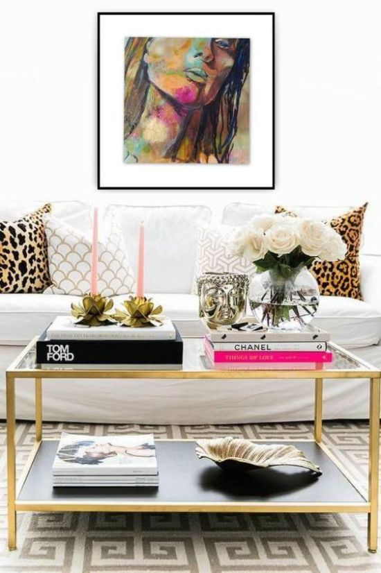 Glam Black And Gold Coffee Table With Stacks Of Books And Pink Candles