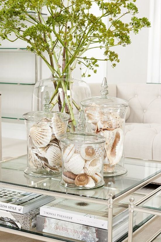 Glass Coffee Table With Books And Large Jars With Seashells
