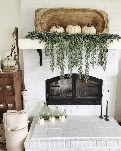 Home Decor Trend Ideas For Fall 2019 With A Mantel Decorated With Cascading Greenery And Three White Pumpkins And A Dough Bowl
