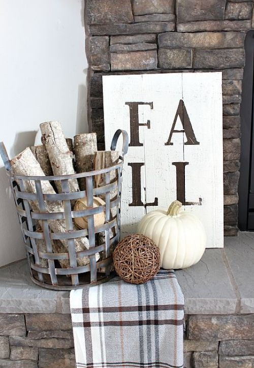 Home Decor Trend Ideas For Fall 2019 With A Metal Basket With Branches And A Plaid Blanket Plus A Vine Ball With A White Pumpkin And A Sign