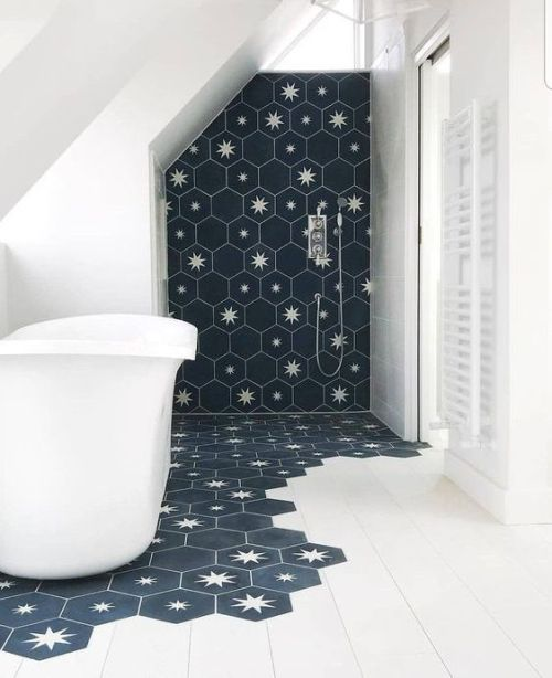 Laconic Bathroom Done With White Tiles And Navy Hexagon Tiles With Stars That Come Under The Tub