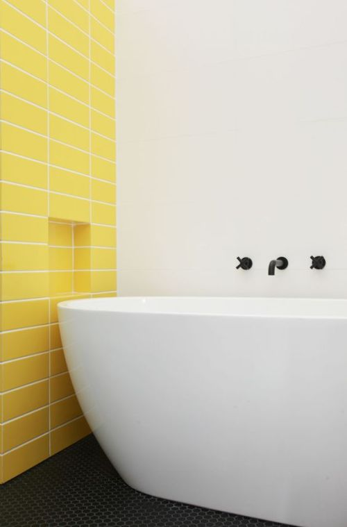 Minimalist Bathroom With A Statement Yellow Tile Wall And A Neutral And Sleek Bathtub