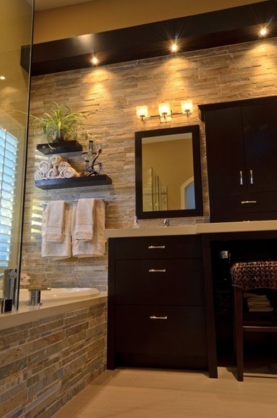Modern Bathroom Done With Decorative Stone And Dark Furniture Plus Lights For A Contrasting And Bold Look