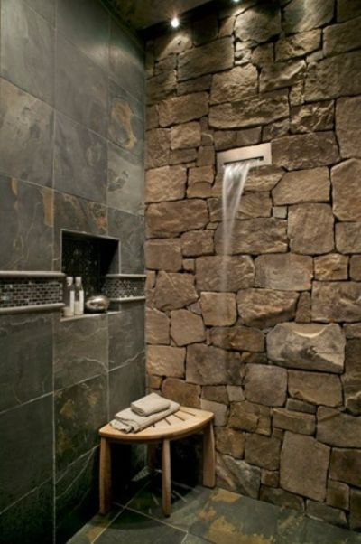 Natural Shower Space With A Stone Wall And Dark Tiles