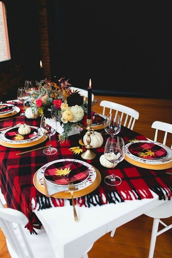 A Bold Thanksgiving Tablescape With A Plaid Blanket And Plates Tall Candles Fall Leaves And Pumpkins Plus Florals
