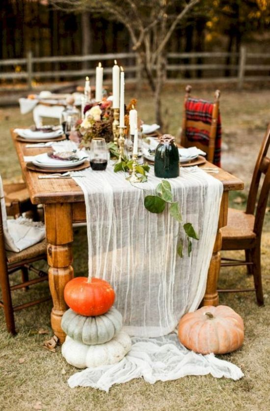 A Chic Natural Thanksgiving Table With A Runner Fresh Pumpkins Tall Candles And Some Leaves And Vases